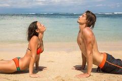 Couplez faire des exercices de yoga et de relaxation par la mer Images stock