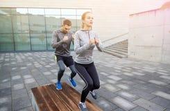 Couplez faire l'exercice d'étape sur le banc de rue de ville Photos stock