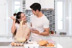Couplez faire la boulangerie, le gâteau dans la chambre de cuisine, le jeune homme asiatique et la femme ensemble Images libres de droits