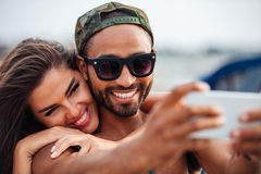 Couplez faire la photo de selfie sur le smartphone à la jetée de mer Photographie stock libre de droits