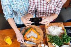 Couplez faire le coeur avec des carottes et prendre des photos utilisant le smartphone Image libre de droits