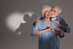 Couplez faire le geste et la position d'amour dans le studio avec l'ombre en forme de coeur Images libres de droits