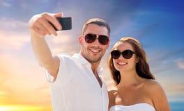 Couplez faire le selfie par le smartphone au-dessus du ciel de coucher du soleil Image stock