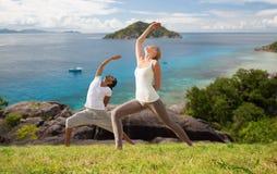 Couplez faire le yoga au-dessus du fond naturel et de la mer Image libre de droits