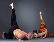 Couplez faire le yoga dans le studio, sur le fond gris Photos stock