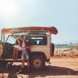 Couplez faire une pause pour regarder la carte tandis que sur la promenade en voiture Photo libre de droits