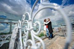 Couplez heureux dans l'amour étreignant près de la photo de mode de vie de mode de balustrade Image libre de droits
