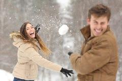 Couplez jouer avec la neige et l'amie jetant une boule Photographie stock