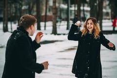 Couplez jouer avec la neige et l'amie jetant une boule en quelques vacances d'hiver Images stock