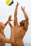 Couplez jouer avec une boule sur la plage Image stock