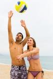 Couplez jouer avec une boule sur la plage Photographie stock libre de droits