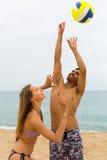 Couplez jouer avec une boule sur la plage Photographie stock