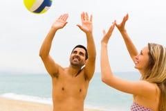 Couplez jouer avec une boule sur la plage Photos libres de droits