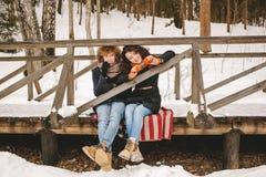 Couplez jouer l'harmonica ensemble en parc d'hiver se reposant sur le floo Image libre de droits