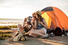 Couplez jouer la guitare et manger les guimauves fryed près de la tente touristique Photos libres de droits