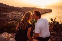 Couplez kitting sur la roche le soir sur le bord de la mer Photos stock