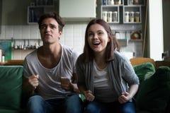 Couplez l'équipe gagnante de soutien encourageante observant le jeu de TV à la maison Image libre de droits