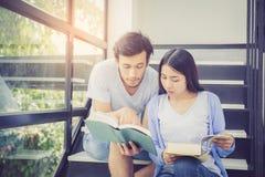 Couplez l'homme bel asiatique et le beau livre de lecture de femme Image libre de droits