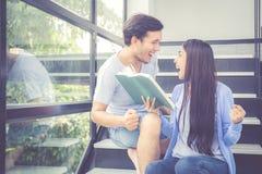 Couplez l'homme bel asiatique et le beau livre de lecture de femme et heureux à la maison Images libres de droits
