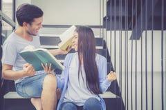Couplez l'homme bel asiatique et le beau livre de lecture de femme et heureux à la maison Photos libres de droits