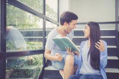 Couplez l'homme bel asiatique et le beau livre de lecture de femme et heureux à la maison Image stock