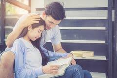 Couplez l'homme bel asiatique et le beau livre et le sourire de lecture de femme Photo stock