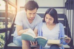 Couplez l'homme bel asiatique et le beau livre et le sourire de lecture de femme Photographie stock libre de droits