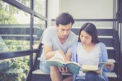 Couplez l'homme bel asiatique et le beau livre et le sourire de lecture de femme Photo libre de droits