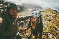 Couplez l'homme de selfie de voyage et la femme trimardant en montagnes aiment et risquent Images stock