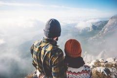 Couplez l'homme et la femme étreignant avec des montagnes et des nuages aménagent en parc Image stock
