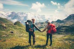 Couplez l'homme et la femme avec le sac à dos tenant des mains Photographie stock
