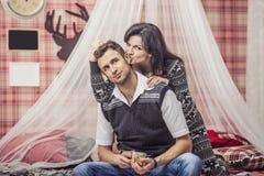 Couplez l'homme et la femme dans la chambre à coucher à la maison buvant du thé avec du Bi Image stock