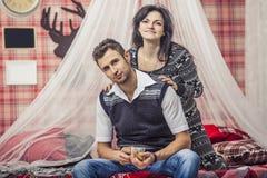 Couplez l'homme et la femme dans la chambre à coucher à la maison buvant du thé avec du Bi Photos libres de droits
