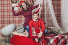 Couplez l'homme et la femme dans la chambre à coucher sur le lit avec une couverture Photographie stock libre de droits