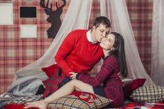 Couplez l'homme et la femme dans la chambre à coucher sur le lit avec une couverture Photo stock