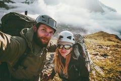 Couplez l'homme et la femme de selfie de voyage trimardant en montagnes Image stock