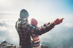 Couplez l'homme et la femme jugeant des mains augmentées sur le sommet de montagne Photos libres de droits