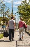 Couplez l'homme et la femme marchant avec des sacs de sport Photos libres de droits