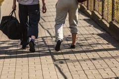 Couplez l'homme et la femme marchant avec des sacs de sport Photo libre de droits