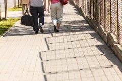 Couplez l'homme et la femme marchant avec des sacs de sport Images stock