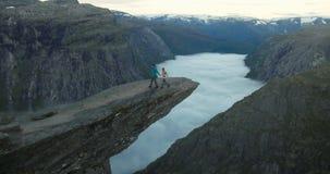 Couplez l'homme et la femme sur des montagnes de falaise de Trolltunga aiment et voyagent clips vidéos