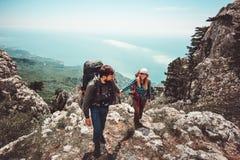 Couplez l'homme et la femme tenant des mains augmentant aux montagnes Image stock