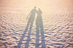 Couplez l'ombre sur la plage, éclairage de coucher du soleil, concept de vacances d'été peu commun Photo stock