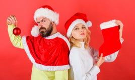 Couplez la chaussette de prise de costume de Santa de Noël et la boule d'ornement Femme et homme barbu dans Noël de attente de ch images stock