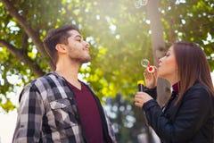 Couplez la détente en parc avec le ventilateur de bulle Le printemps… a monté des feuilles, fond naturel Photos stock