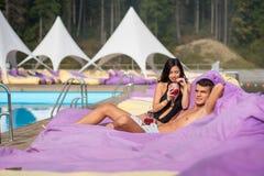 Couplez la détente près de la piscine sur les canapés amortis avec des boissons au lieu de villégiature luxueux Images libres de droits