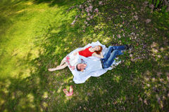 Couplez la détente sur l'herbe dans le jardin de floraison de ressort Photo stock