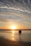 Couplez la détente sur la belle plage au lever de soleil Images stock