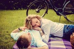 Couplez la détente sur une pelouse après l'équitation de vélo Photo libre de droits
