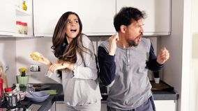 Couplez la danse dans des pyjamas dans la cuisine comme le mouvement lent fou banque de vidéos
